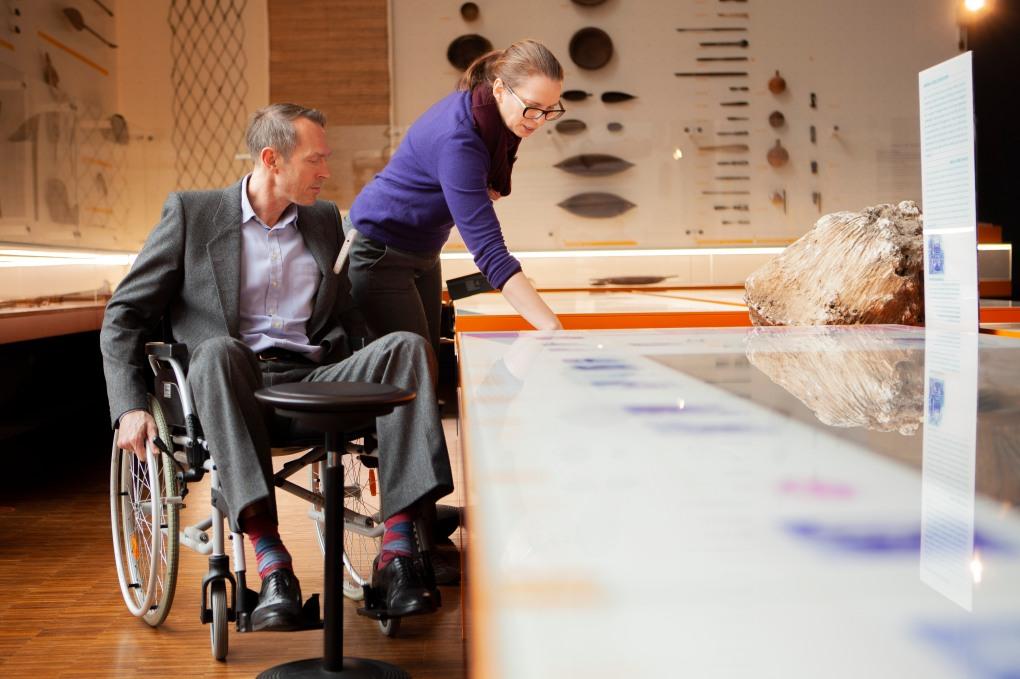 MiQua Direktor Thomas Otten testet im Rollstuhl sitzend einen Multimedia-Tisch in der Ausstellung. Wie unterschiedlich die Perspektive ist, wird über eine Kollegin deutlich, die neben ihm steht.