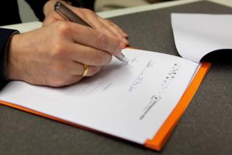 Nahaufnahme der unterschreibenden Hand von APG-Direktor Marco Lohmann.