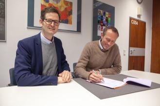 Die Direktoren von APG und MiQua, Marco Lohmann und Thomas Otten, sitzen an einem weißen Tisch und sehen die Kooperationsvereinbarung durch. Beide lächeln und schauen seitlich in Richtung des Fotografen. Im Hintergrund hängen Gemälde an der Wand des Büros.