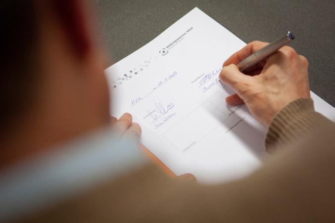 Im Vordergrund verschwommen die Schulter des MiQua-Direktors, im Bildzentrum die Kooperationsvereinbarung, die Thomas Otten gerade unterschreibt.