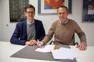 Der Direktor des APG Marco Lohmann, links und Thomas Otten, Direktor des MiQua rechts im Bild, sitzen an einem weißen Tisch und unterzeichnen die Kooperationsvereinbarung. Beide schauen gut gelaunt in die Kamera. Im Hintergrund hängen Gemälde an der Wand des Büros.
