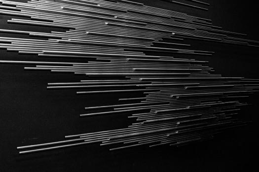 Auf der Bühne der Aula im Apostelgymnasium wurde ein Gruppenfoto mit allen Anwesenden aufgenommen. Im Hintergrund an der Wand ist das Relief, die sogenannte Flächenbahn von Norbert Kricke angebracht. Mehrere horizontal angeordnete Stäbe in unterschiedlichen Längen auf schwarzem Untergrund bilden das Kunstwerk. Dieses Bild ist eine Nahaufnahme des Reliefs.