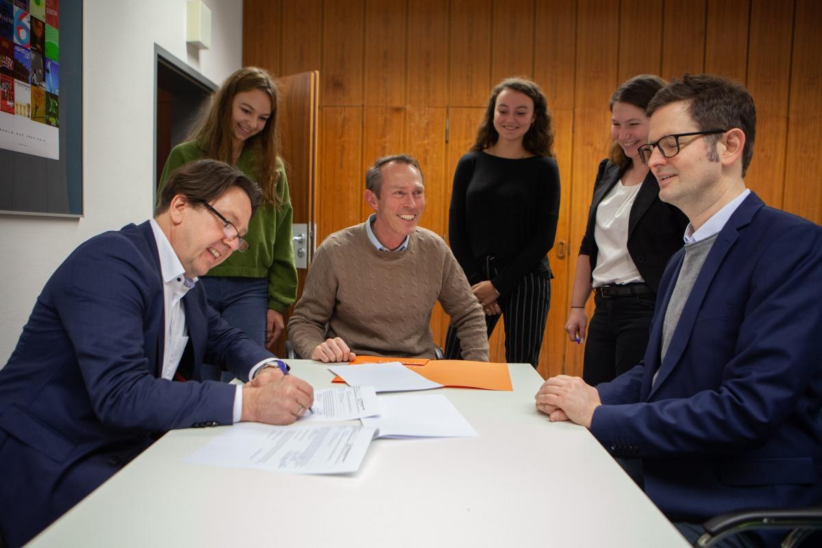 Frank Schweppenstette, links im Bild, sitzt am Konferenztisch und unterschreibt die Kooperationsvereinbarung zur Bildungspartnerschaft. Ebenfalls dabei sind die anderen Unterzeichner*innen. Sie alle sind um den Tisch versammelt und gut gelaunt.