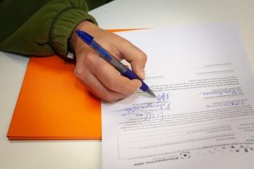 Nahaufnahme von der rechten Hand einer Schülerin, die gerade die Vereinbarung mit einem blauen Kugelschreiber unterzeichnet. Am Bildrand ist noch der Beginn ihres Pullover Ärmels zu sehen.