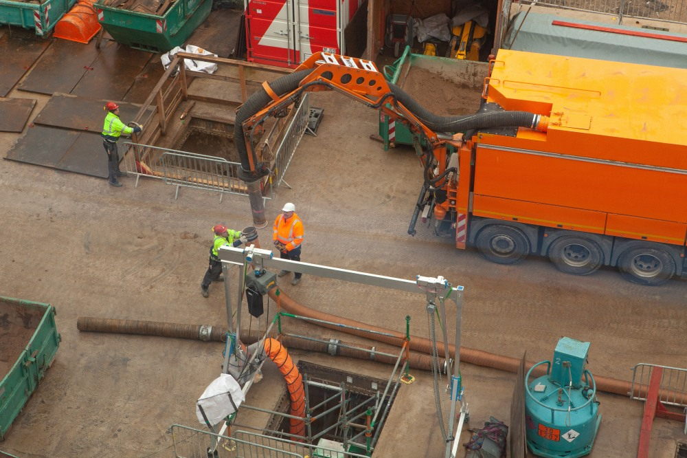 Mithilfe des Saugrüssels entfernen Bauarbeiter den Sand aus den archäologischen Befunden im Untergrund. Die Situation im Bild zeigt Bauarbeiter, die den Schlauch in eine Öffnung im Boden lenken wollen.