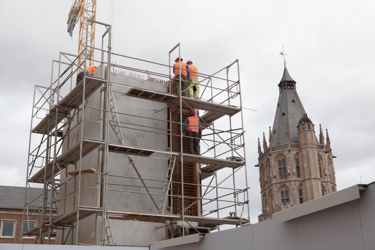 Auf der Baustelle ist im Moment einiges los. Unter anderem wird einer der Aufzüge gebaut und ragt wie ein Turm nach oben. Und wo gearbeitet wird, da sind auch Bauarbeiter. Aus der Froschperspektive aufgenommen, zeigt das Bild Bauarbeiter ganz oben auf dem Gerüst am Aufzugschacht. Rechts ins Bild ragt noch der obere Teil des Rathausturmes.