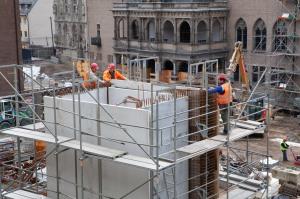 Auf der Baustelle ist im Moment einiges los. Unter anderem wird einer der Aufzüge gebaut und ragt wie ein Turm nach oben. Und wo gearbeitet wird, da sind auch Bauarbeiter. Auf nahezu gleicher Höhe aus einem der umliegenden Gebäude aufgenommen, zeigt das Bild Bauarbeiter ganz oben auf dem Gerüst am Aufzugschacht. Im Hintergrund ist die Renaissance-Laube zu sehen.