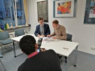 Im Vordergrund des Bildes positioniert sich der Fotograf, um die beiden Direktoren bei der Unterzeichnung abzulichten. Die beiden Herren sitzen im Bildzentrum an einem Tisch und sehen das zu unterzeichnende Papier durch. Der Fotograf ist nur von hinten zu sehen.