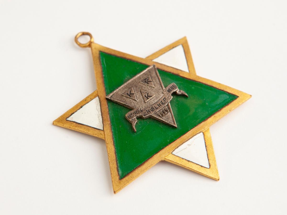 """Der Karnevalsorden hat die Form eines Davidsterns in den Farben grün und weiß mit einer kleinen Öse an der oberen Spitze. Im Zentrum ist zusätzlich das Emblem des Vereins """"Kleiner Kölner Klub"""" sowie die Jahreszahl 1929 aufgebracht."""