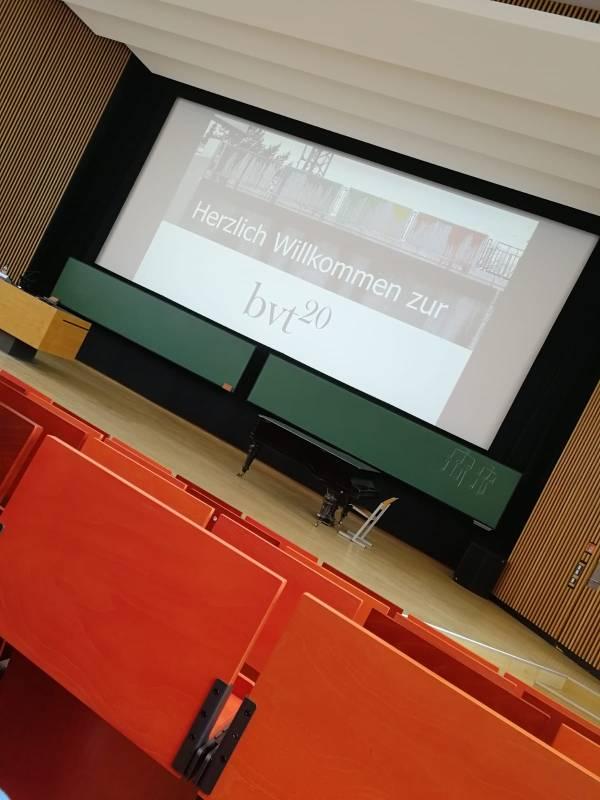 Noch ist der Saal zwar nicht mit Teilnehmenden gefüllt, aber das Titelblatt der Präsentation auf der Bühne heißt alle willkommen.