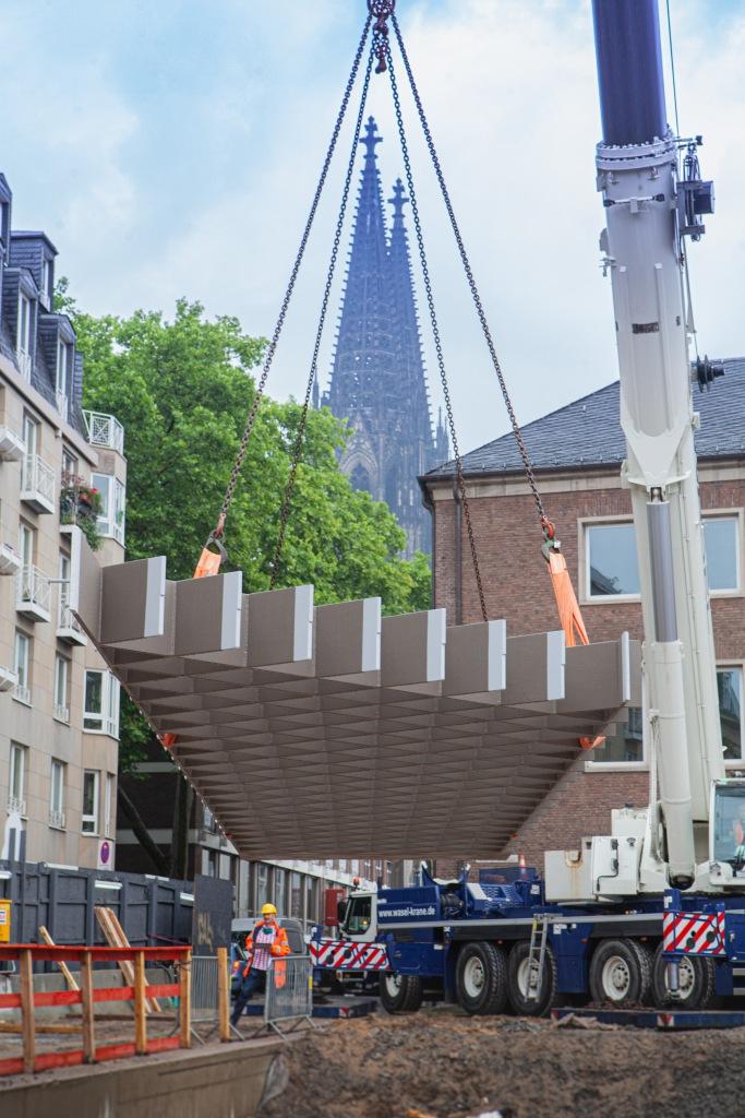 Ein Schwerlastkran hat ein großes Stahlelement für das Museum in die Luft gehoben. Im Hintergrund die Türme des Kölner Doms