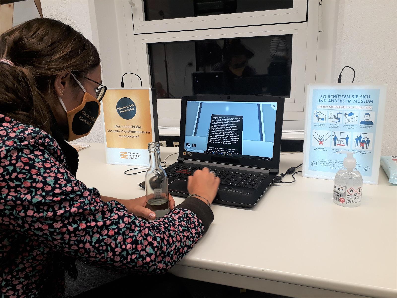 Eine Teilnehmerin sitzt an einem der Tische und testet die Anwendung an einem Laptop.