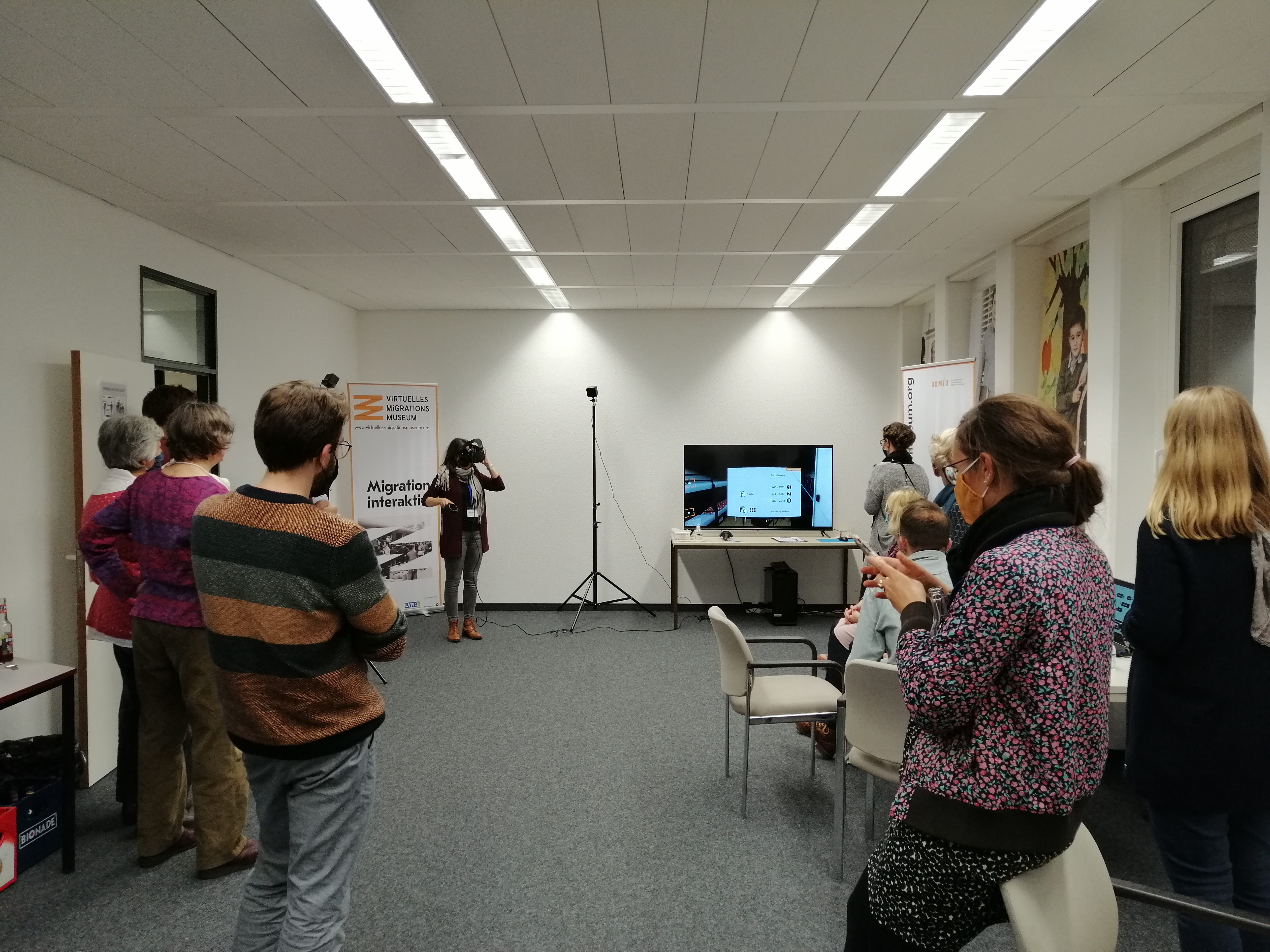 Blick in den Veranstaltungsraum des DOMiD. Am linken und rechten Bildrand verteilt stehen die Teilnehmer*innen und folgen der Präsentation von Sandra Vacca. Sie - hinten links im Bild mit VR-Brille und Steuerung - zeigt über einen Bildschirm wie die Anwendung als Virtual Reality-Angebot funktioniert.