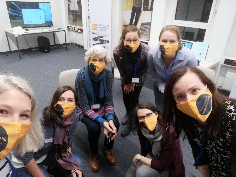 Ein Selfie vom Organisationsteam zum Abschluss der Veranstaltung. Die 7 Organisatorinnen lächeln mit unseren Masken im Veranstaltungsdesign in die Kamera.