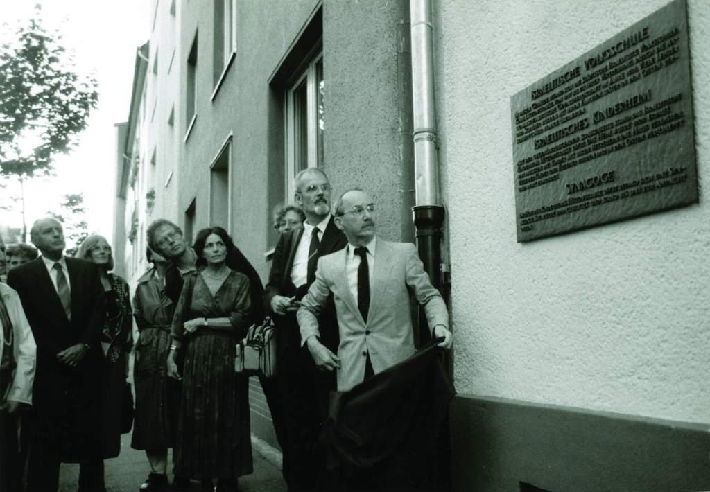 Das Bild zeigt die Situation der Enthüllung der Gedenktafel durch Henry Gruen im Jahr 1988. Rechts im Bild ist die Tafel für die ehemalige Israelitische Volksschule. Links davor stehen mehrere Menschen und sehen bei der Enthüllung zu.