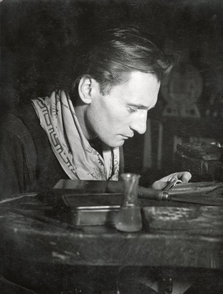 Schwarz-Weiß Aufnahme des Goldschmieds Fritz Deutsch beim konzentrierten Arbeiten in einer Werkstatt.