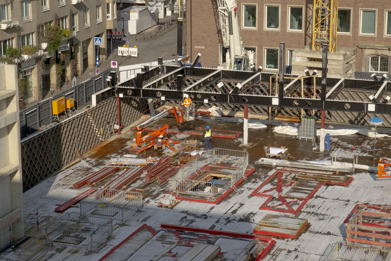 Die MiQua Baustelle ist Anfang Februar mit einer dünnen Schnee- oder Eisschicht überzogen. Der Blick von Süden auf den Baustellenabschnitt an der Portalsgasse und Unter Goldschmied zeigt, dass der Grundriss des späteren Gebäudes schon mit den sogenannten Rautentragwerken, einer Stahlkonstruktion, angezeigt wird. Die Arbeiter auf der Baustelle arbeiten in diesem Moment an einem Querträger, der später das Obergeschoss halten wird. Den oberen Abschluss des Bildes, bildet der Spanische Bau. Links im Bild ist noch einer der Aufzugschächte aus Beton erkennbar.