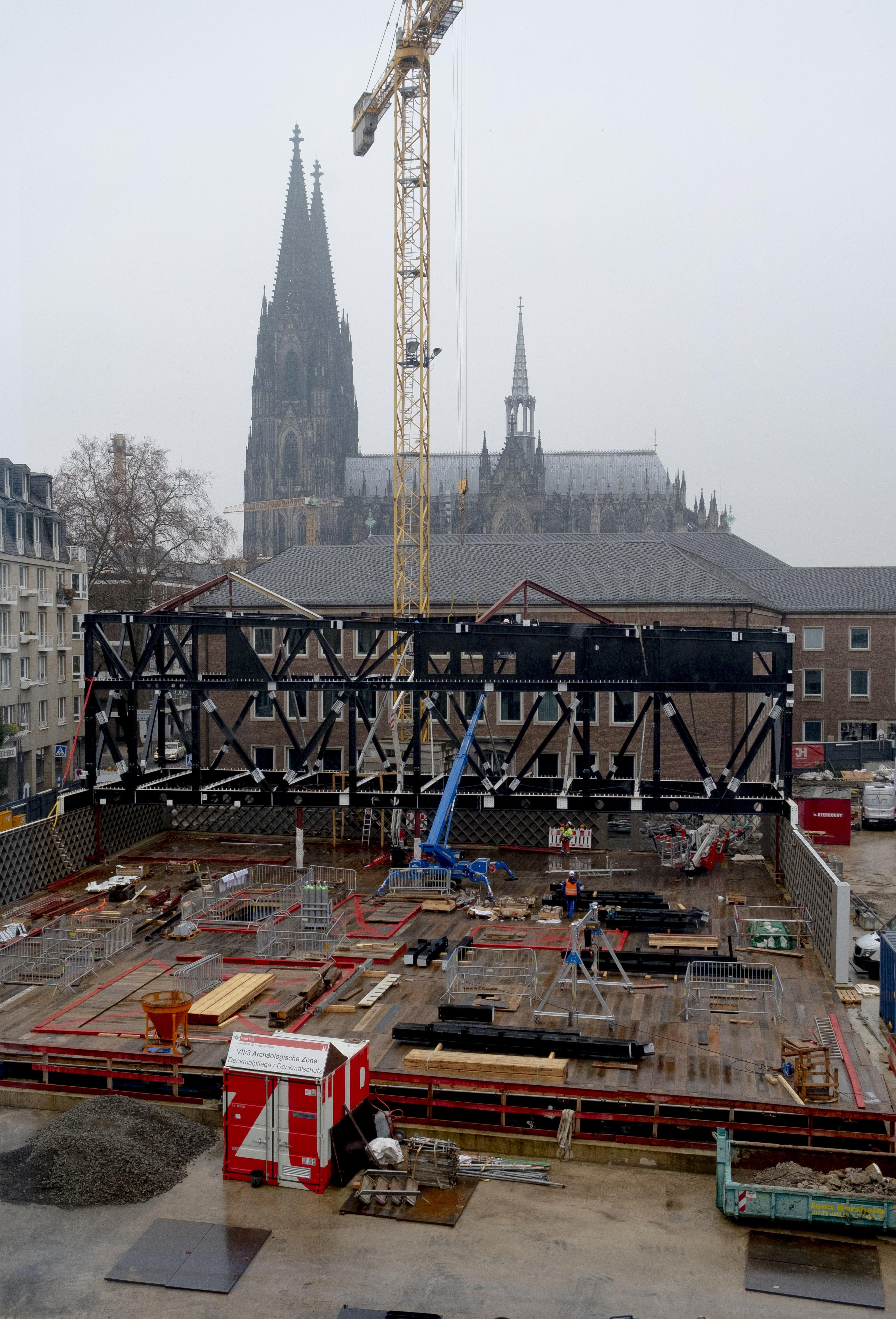 Die MiQua-Baustelle von Süden aus fotografiert. Im Hintergrund ist durch Nebel und vor einem bewölkten Himmel der Kölner Dom zu sehen. Im Zentrum des Bildes liegt die MiQua-Baustelle. Ein hoher gelber Baukran ragt darüber. Die Sicht auf den sogenannten Spanischen Bau wird nun teilweise von einem schwarzen Stahlgerüst verdeckt, das später das Obergeschoss und Dach des Museums halten wird.