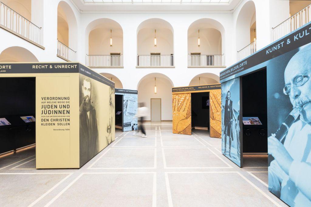 Im lichtdurchfluteten Innenraum des Landeshauses stehen die vier Ausstellungskuben in den Farben gelb, blau, orange und dunkelblau. Sie sind von einem Umgang auf zwei Geschossen mit Bögen und aus hellem Stein umgeben.