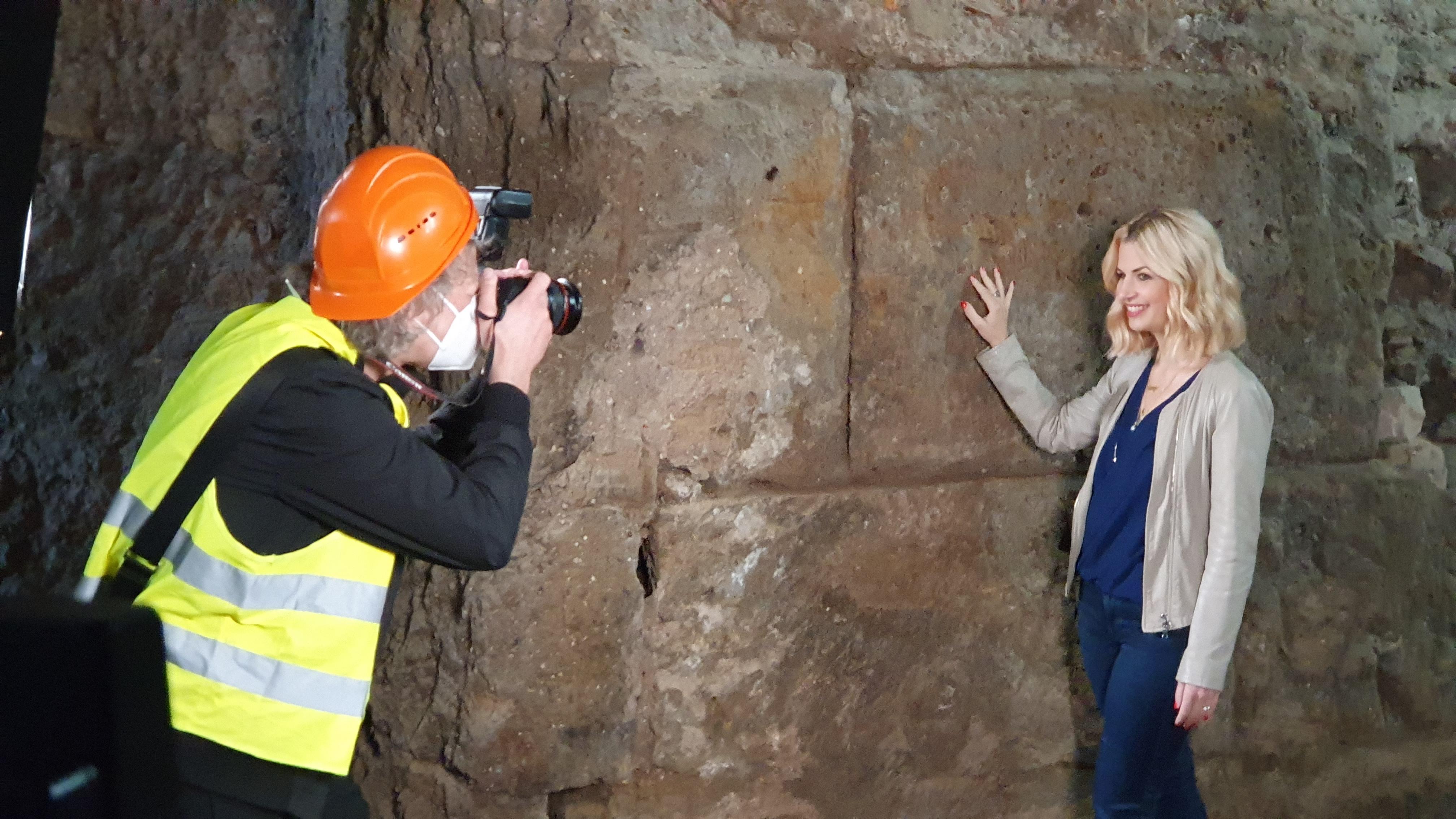 Frau mit blonden Haaren und beige-farbener Jacke lehnt locker an einer Mauer in der archäologischen Grabung. Sie wird von einem Mann mit Bauhelm, Kamera und Warnweste fotografiert.