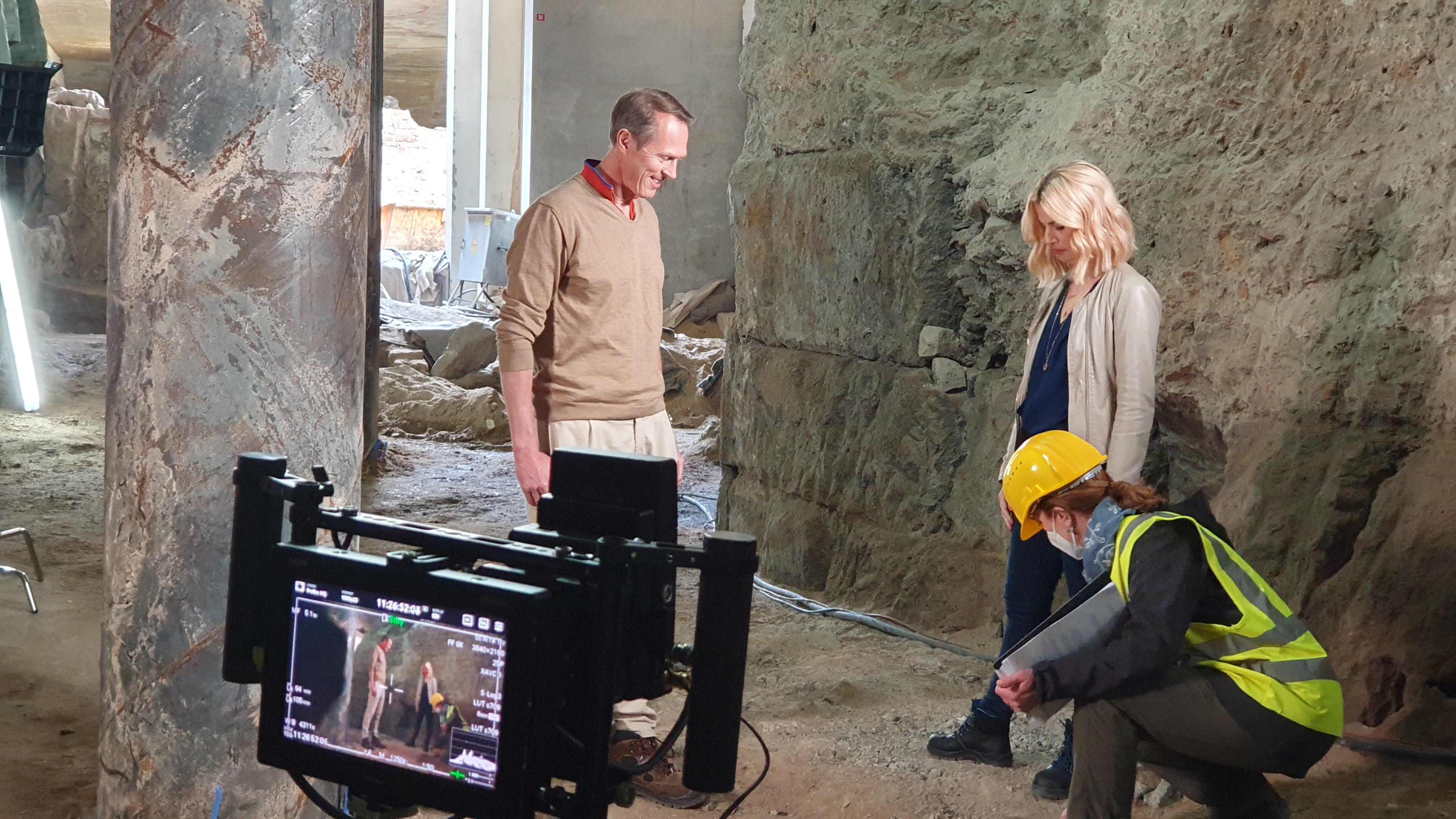 Interviewsituation: Links im Bild Mann mit beige-farbenem Pullover. Frau mit blonden Haaren und beige-farbener Jacke rechts im Bild. Eine Frau mit Bauhelm und Warnweste richtet noch etwas an den Schuhen. Im Vordergrund ist bereits eine Kamera für die Aufnahme ausgerichtet.