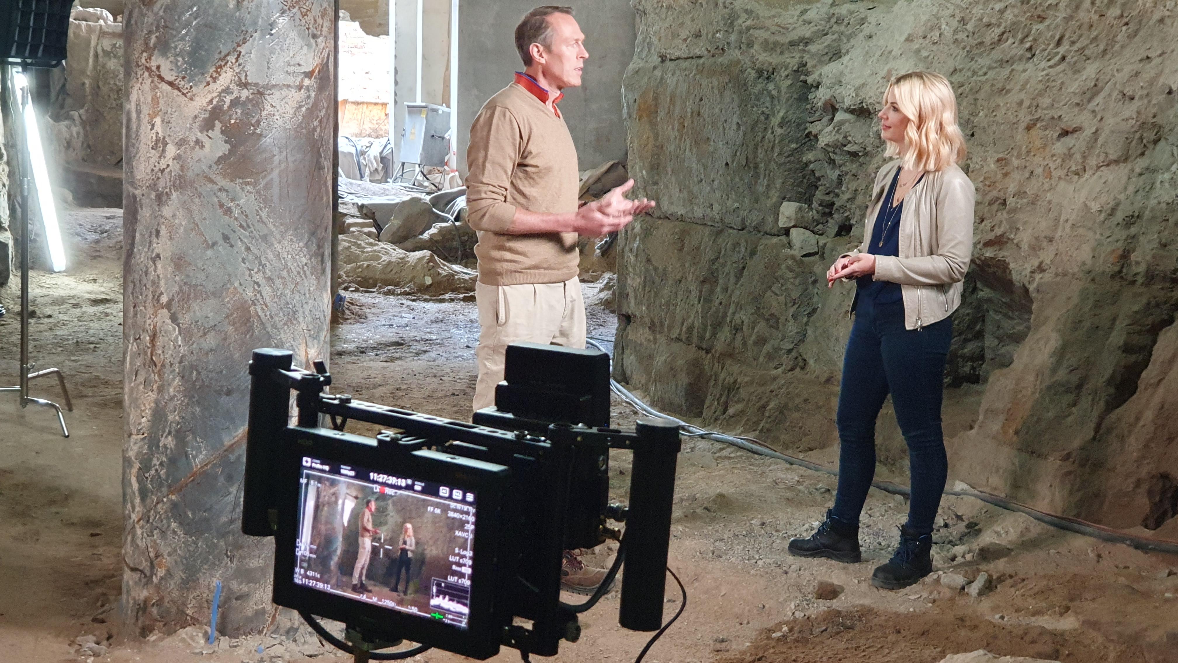 Interviewsituation: Links im Bild Mann mit beige-farbenem Pullover. Frau mit blonden Haaren und beige-farbener Jacke rechts im Bild. Im Vordergrund nimmt eine Kamera die Situation auf.