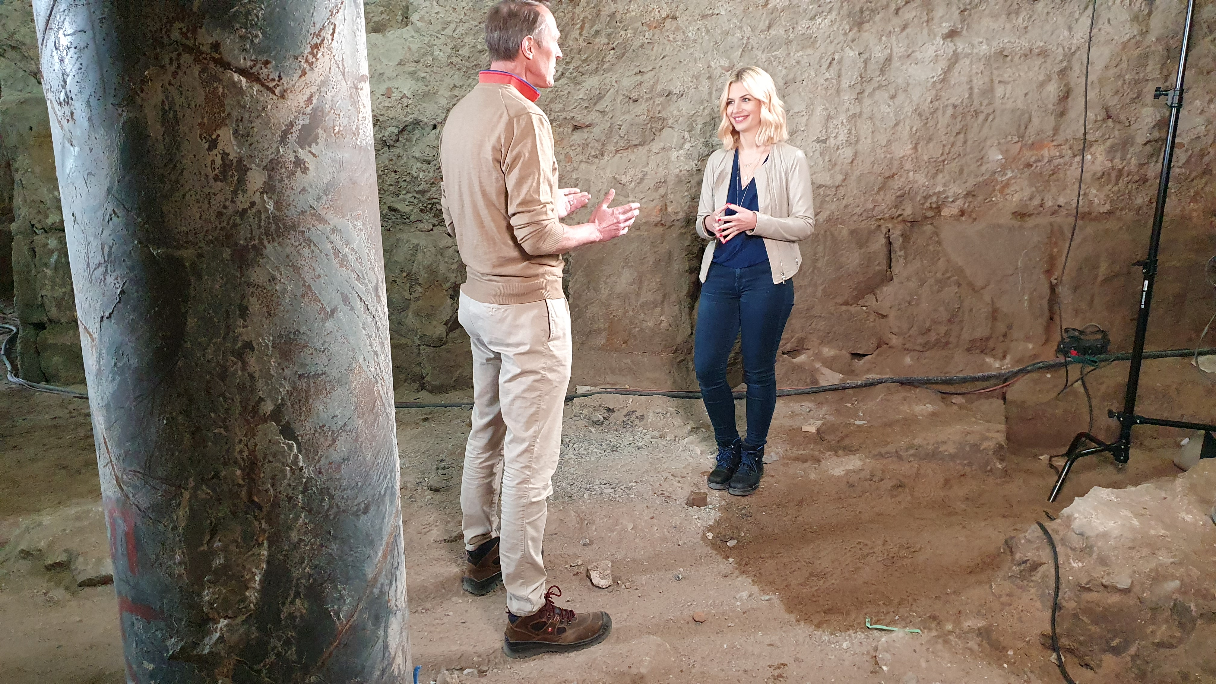 Interviewsituation: Links im Bild Mann mit beige-farbenem Pullover. Frau mit blonden Haaren und beige-farbener Jacke rechts im Bild. Seitliche Perspektive.