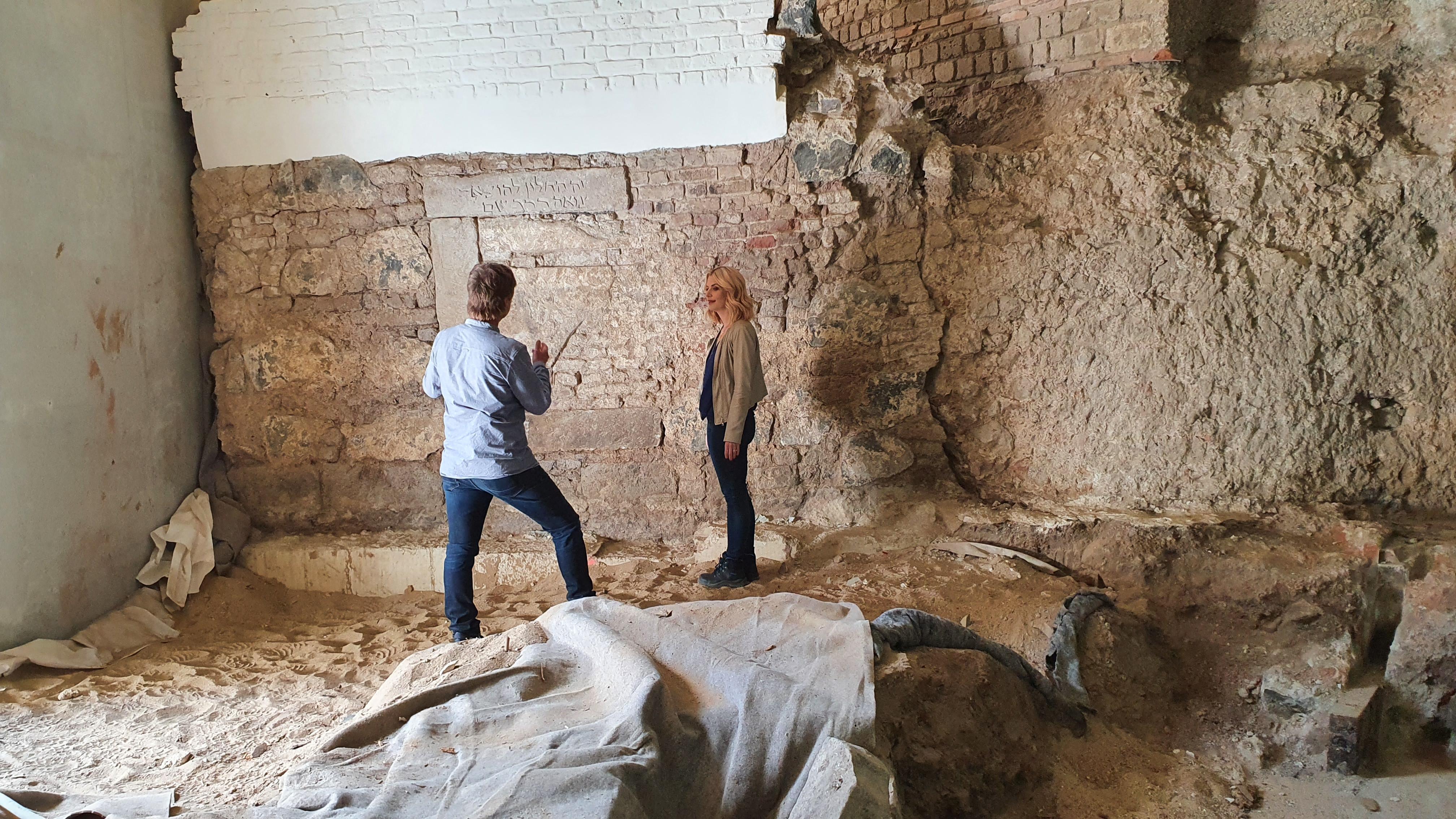 Interviewsituation: Links im Bild Mann mit hellblauem Hemd. Er erklärt einer Frau mit blonden Haaren und beige-farbener Jacke die archäologischen Befunde, die sie umgeben. Im Hintergrund eine hebräische Inschrift.