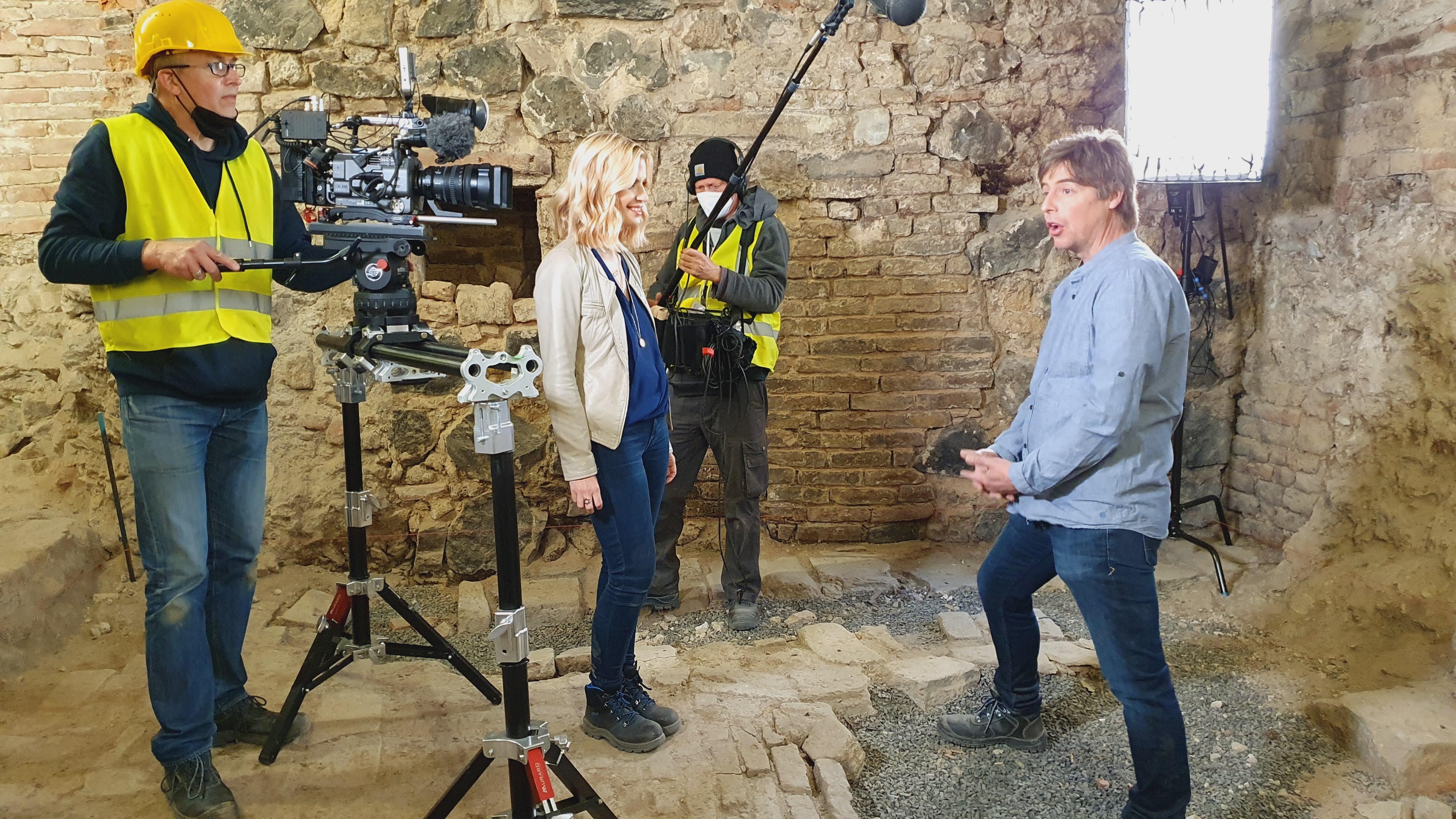 Das Bild zeigt die Situation der Filmaufnahme: Das Kamerateam mit Equipment nimmt das Interview mitten in archäologischen Befunden auf.