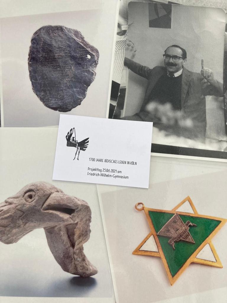 Vier Fotos (mittelalterliche Schiefertafel, Foto eines lachenden Mannes mit Brille und Schnurrbart, steinerner Vogelkopf, Karnevalsorden in Form eines Davidsterns) und eine Einladungskarte mit dem Logo des Friedrich-Wilhelm-Gymnasiums Köln liegen auf einem Tisch.