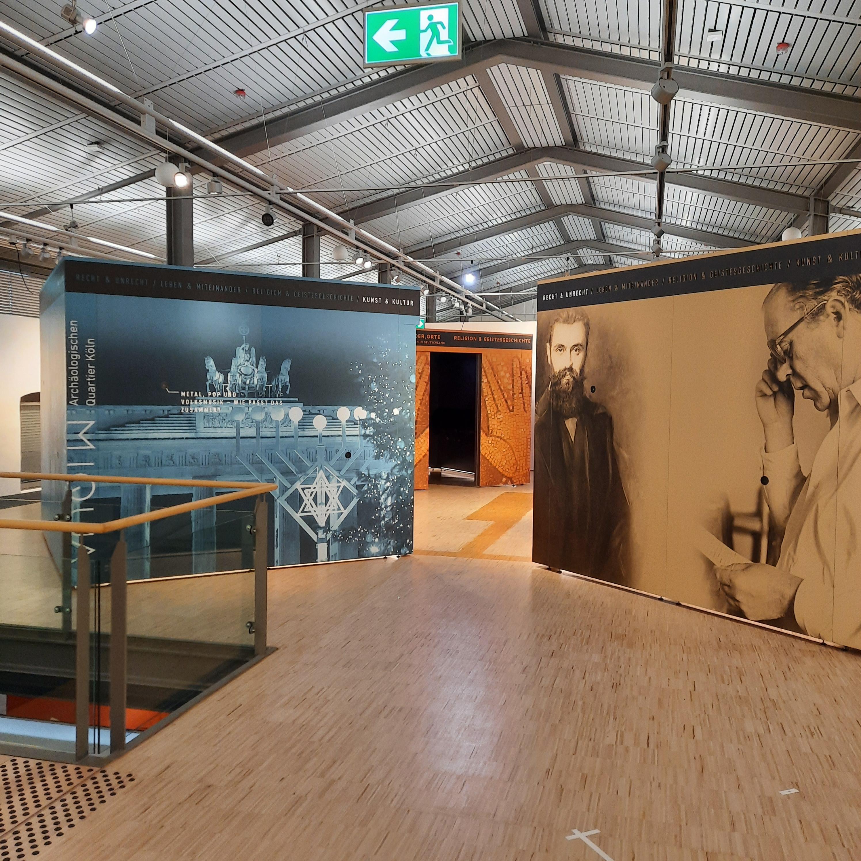 Blick in den Ausstellungsraum: Drei der vier Kuben sind auf diesem Bild unter grauem Dach zu sehen.
