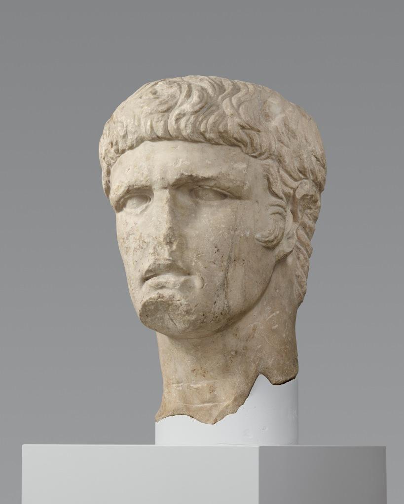 Büste des Kaisers Domitian: Kopf auf Halterung vor grauem Hintergrund.