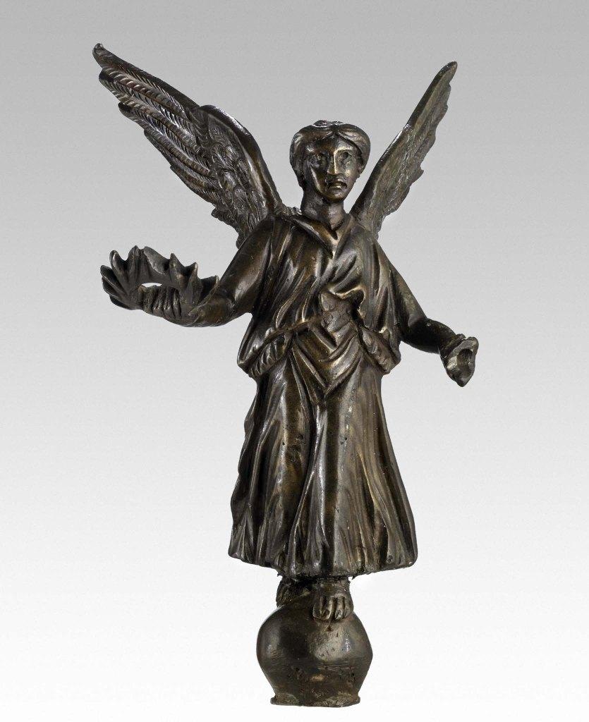 Viktoria-Figur mit Flügeln und Kranz in der rechten Hand, die auf einer Kugel steht.